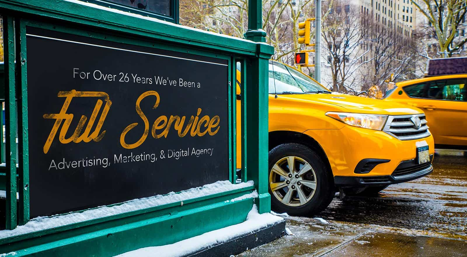 New York City Scene with taxi cap and a sign stating 'For Over 26 Years We've Been a Full Service Advertising, Marketing, & Digital Agency'